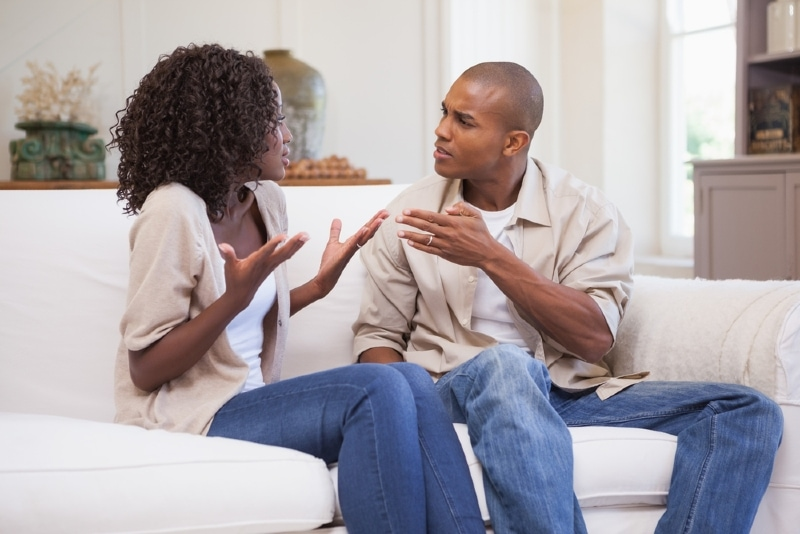 man and woman arguing while sitting on white sofa
