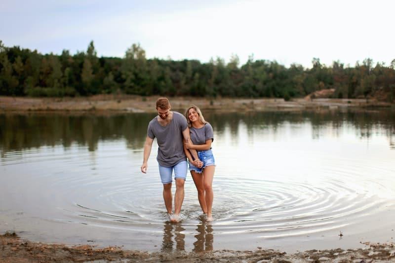 couple enjoying the lake together holding hands wearing denim shorts