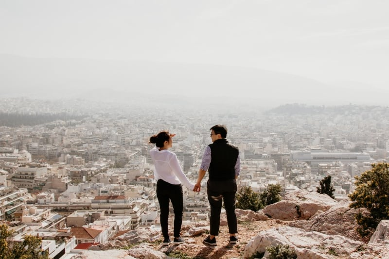 man and woman holding hands while standing on top of cliff