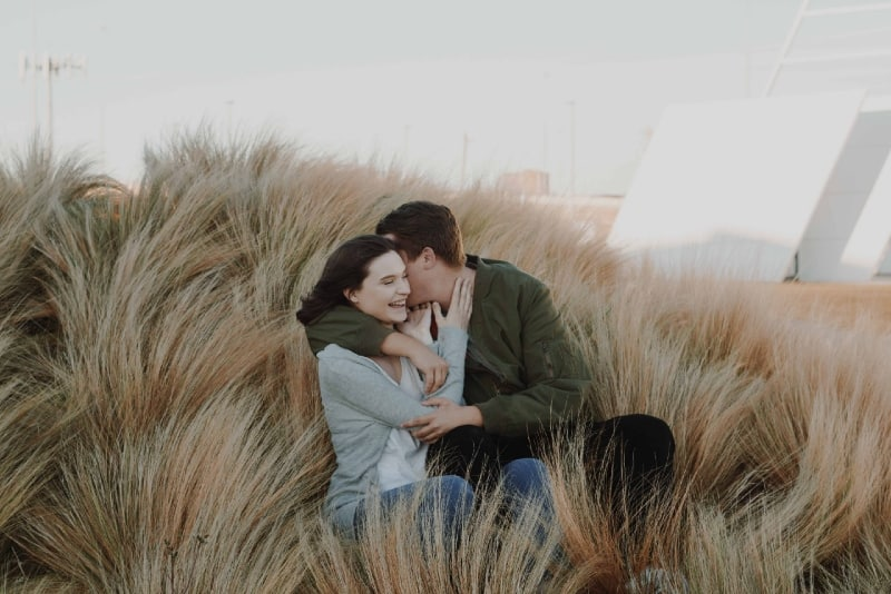 man and woman hugging while sitting on brown grass field