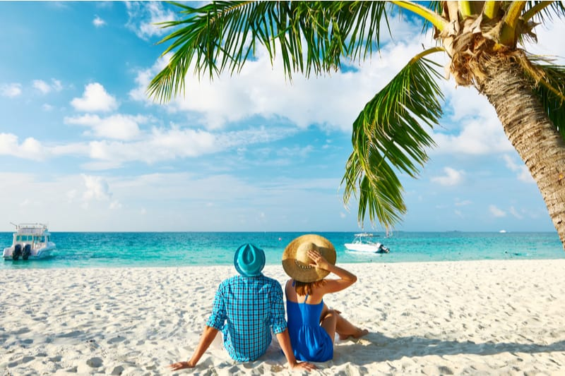 couple in blue and green clothes relaxing in a tropical beach with white sand