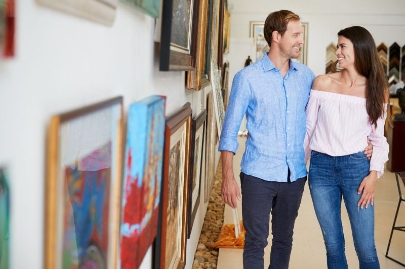 couple inside an art gallery with man's arms around the woman's waist