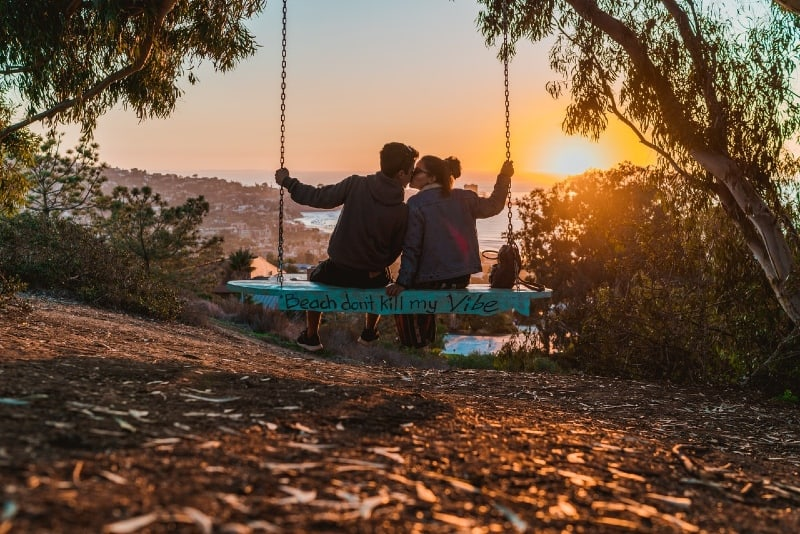 man and woman kissing while sitting on swing during sunset
