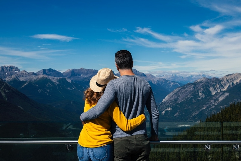 man and woman hugging while looking at mountain