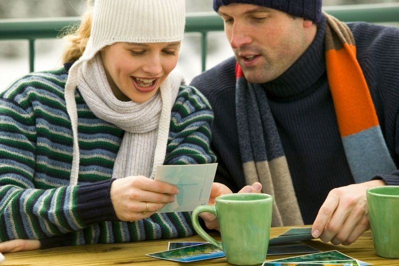 couple looking at pictures outdoors taking coffee while wearing winter clothes