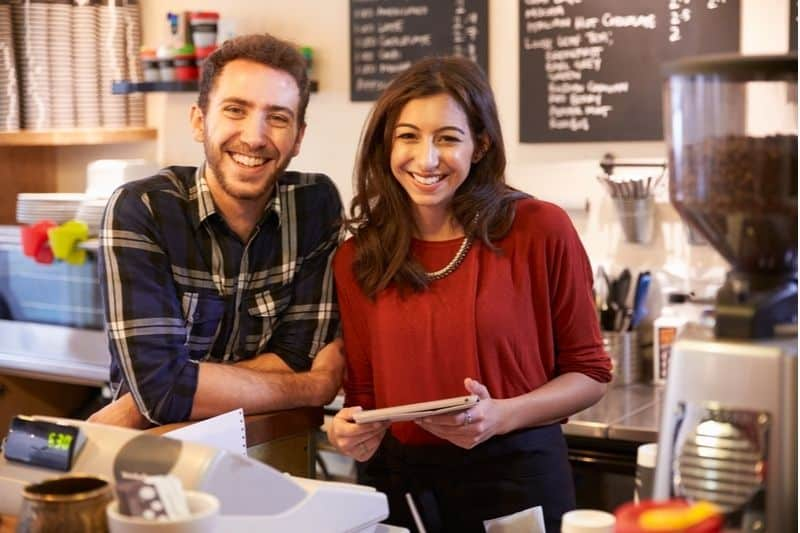 couple running a coffee shop business posing near the cashiers counter