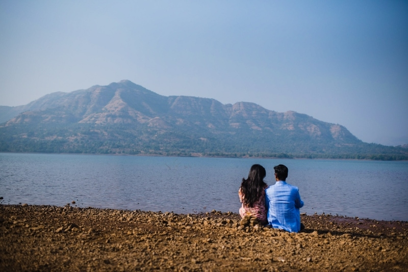 man in blue shirt and woman sitting near river