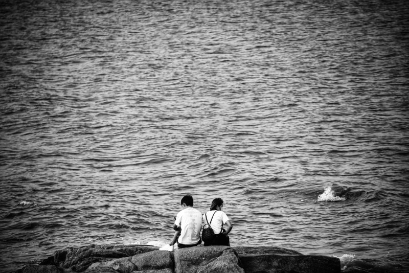 woman with backpack and man sitting near water
