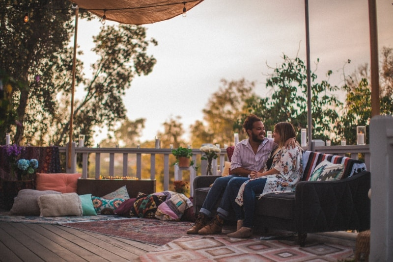 man and woman sitting on couch an talking outdoor
