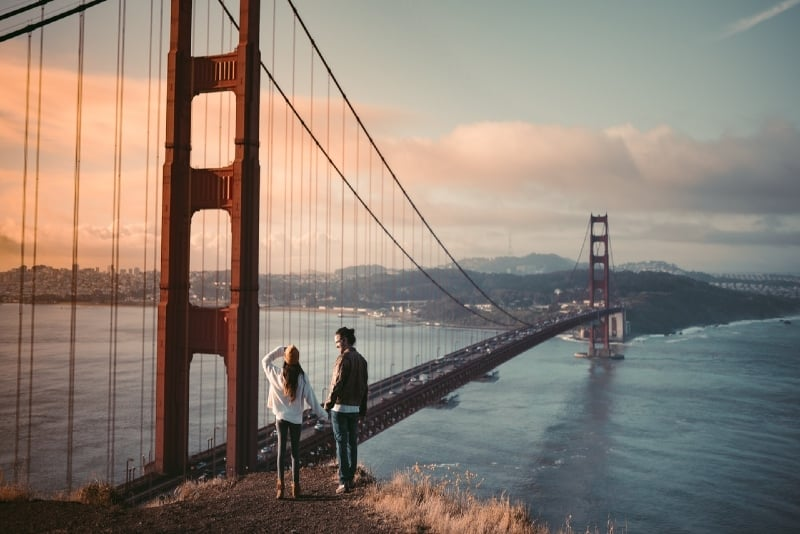 man and woman holding hands standing near golden gate bridge