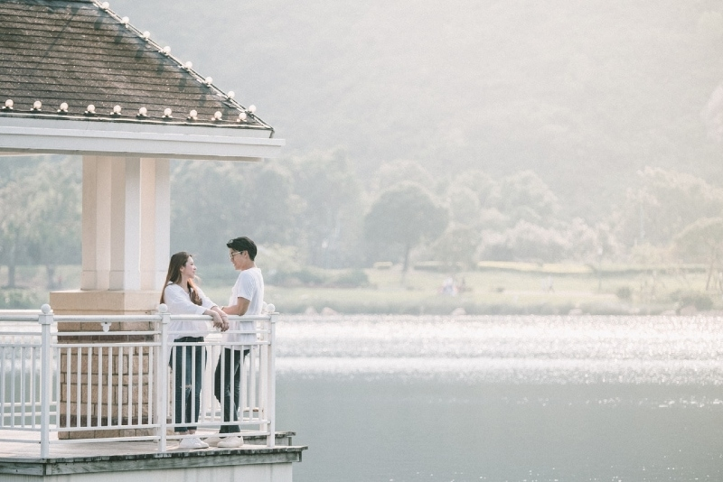 man and woman standing near lake during daytime