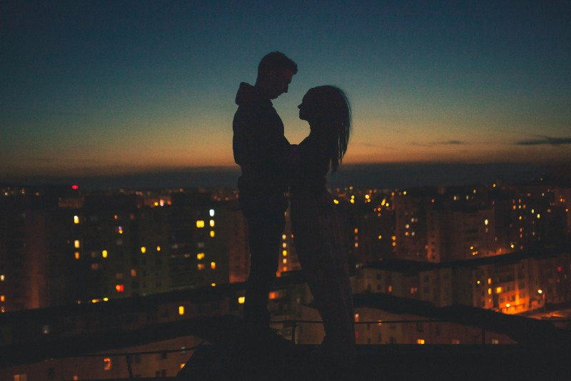 man and woman standing on rooftop during sunset
