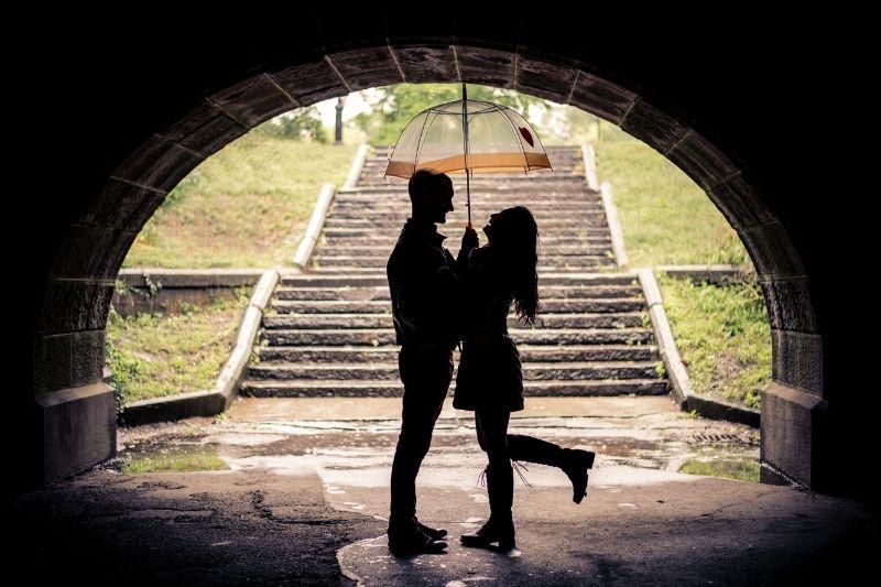 couple under an umbrella during rainy day standing under the bridge
