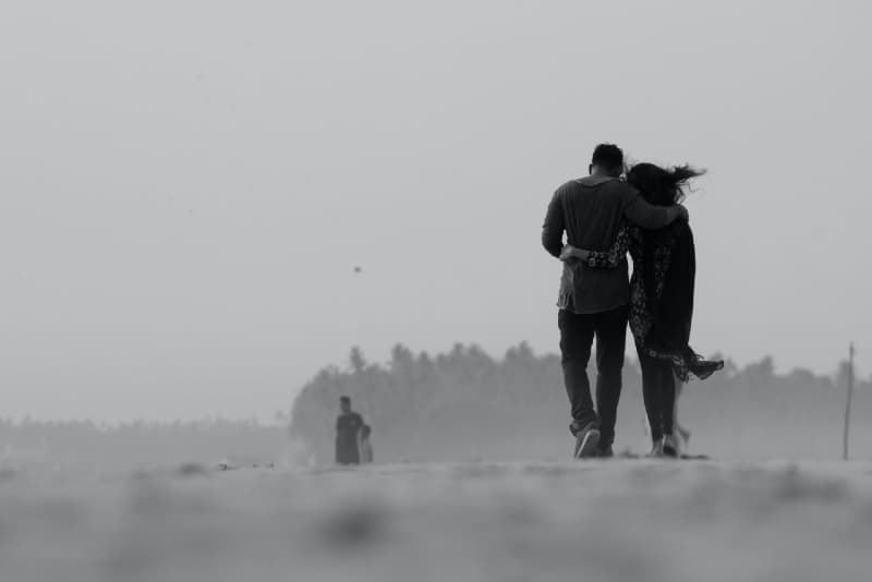 man and woman hugging while walking