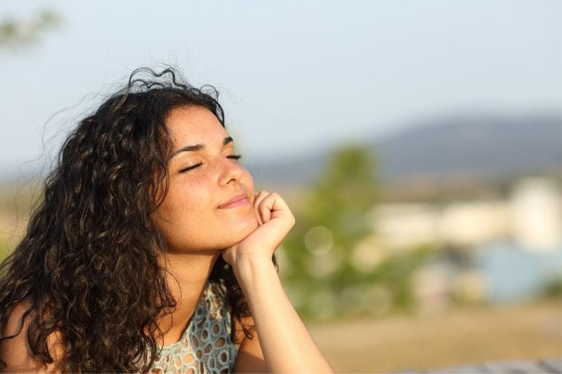 curly hair woman smiling and closing eyes outdoors