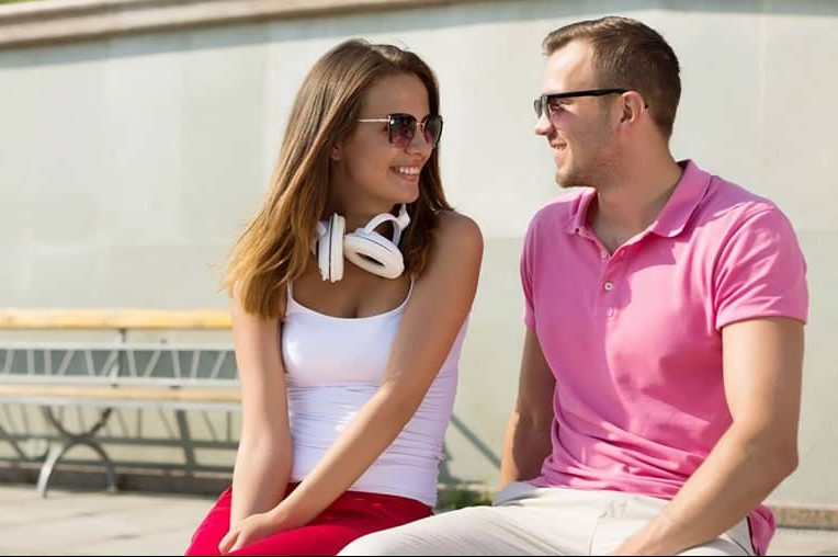 cute woman and man sitting next to each outdoors with woman having headphones around her neck