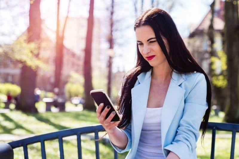 disgusted woman looking at her smartphone outdoors