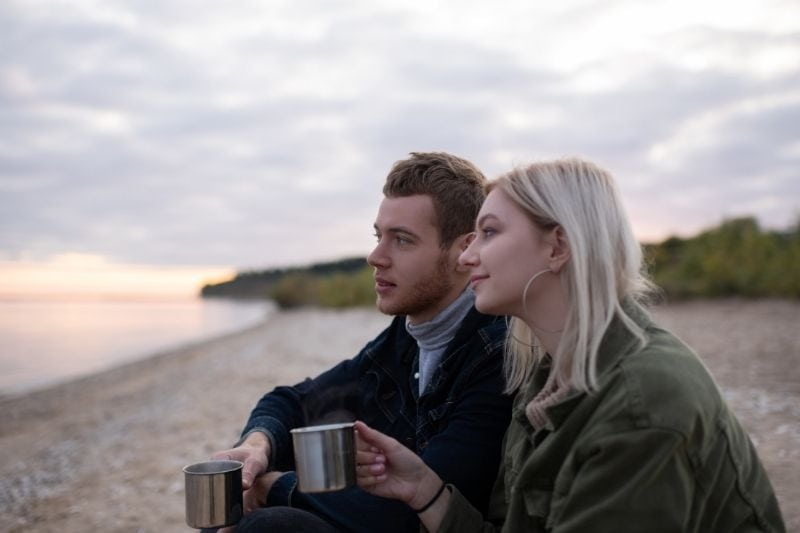 dreamy couple with tea resting in the countryside near a body of water