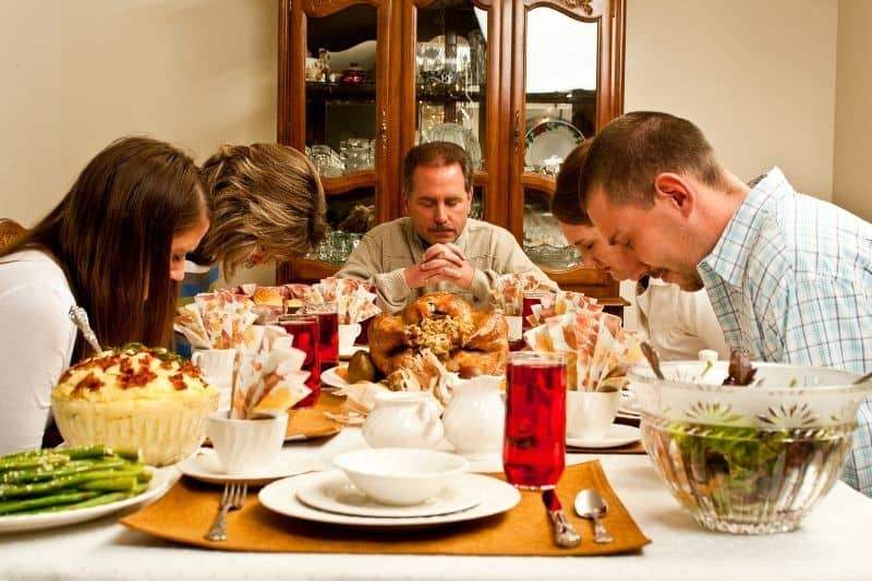 family thanksgiving prayer with table full of festive food