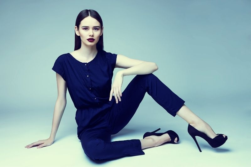 fashionable woman sitting on the floor wearing blue high heels and red lipstick with blue casual wear
