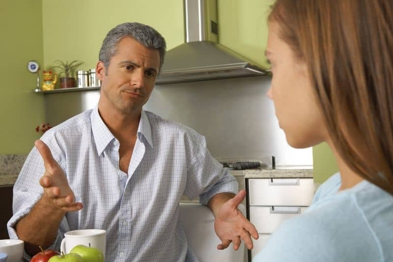 father talking to daughter inside kitchen while sitting by the table