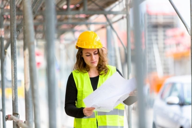 female engineer examining blue print in the construction site