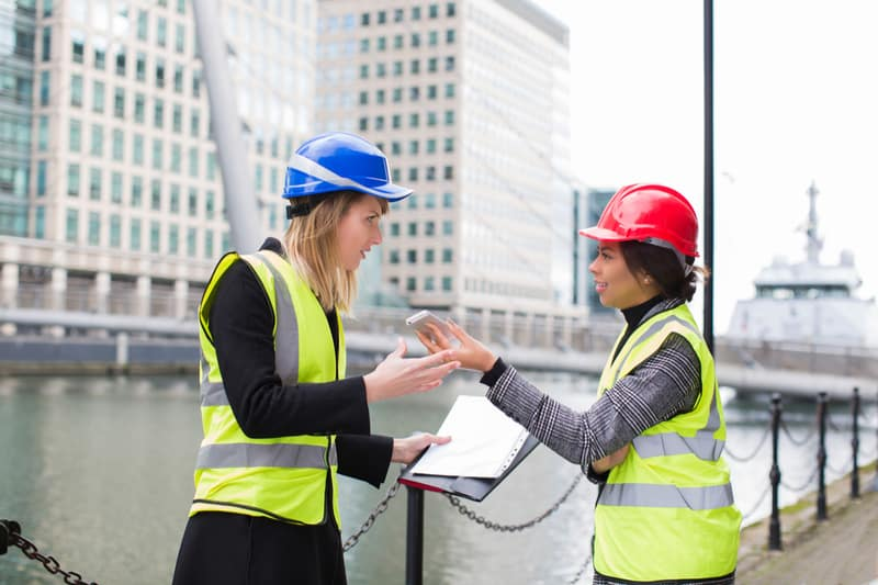female engineers discussing over the cellphone on site location