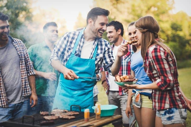 friends having barbecue party outdoors the man grilling let a woman taste
