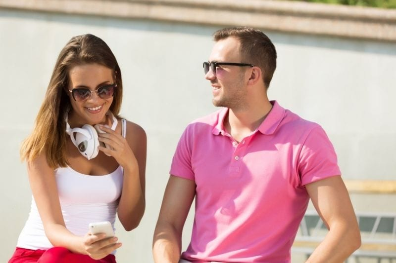 girl looking at her cellphone talking next to a man wearing in pink outdoors