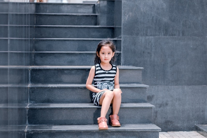 girl in striped dress sitting on stairs
