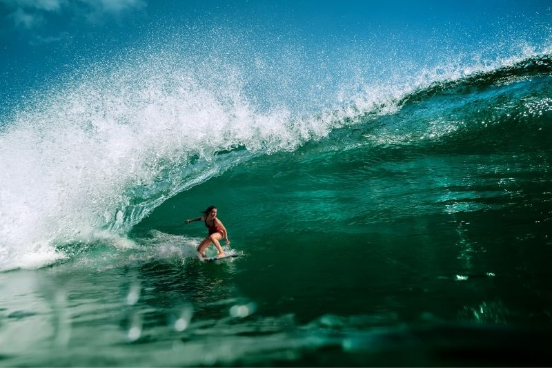 girl surfer riding on a surf over great waves of the ocean
