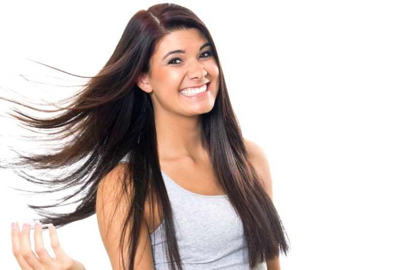 good hair day of a woman smiling flipping her hair standing against a white wall