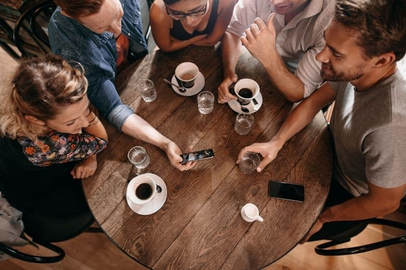 group of friends at a cafe man showing a video from smartphone to friends