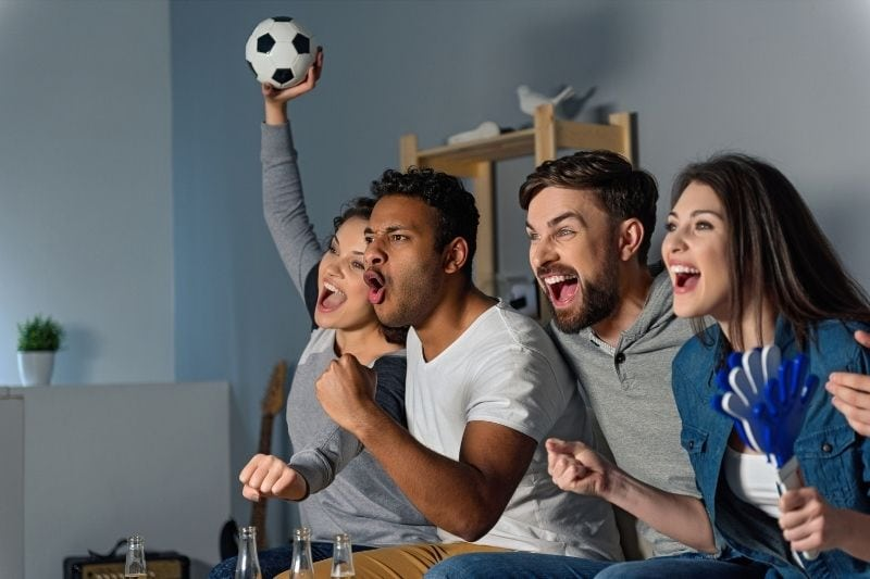 group of friends watching football game with happiness