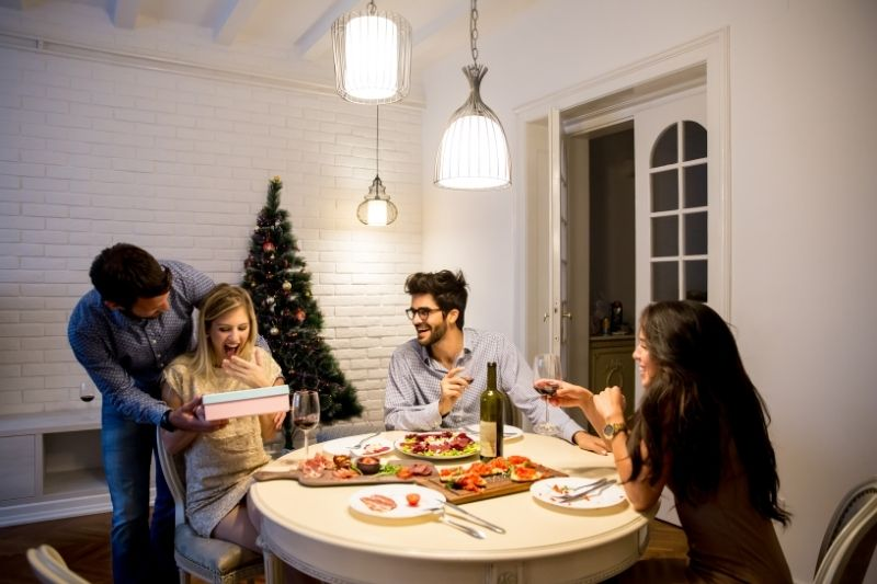 happy young woman receiving gift from a young man with friends during christmas at home