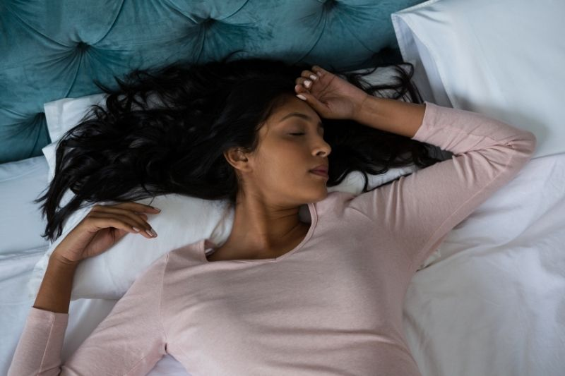 high angle of a woman sleeping in bed with hand on head