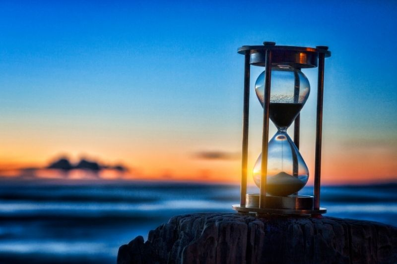hourglass or sand timer in fron of the sea during sunrise of sunset