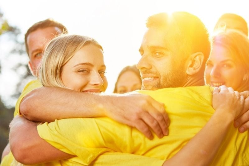 hug in group as a teambuilding event in the community participants wearing yellow shirt
