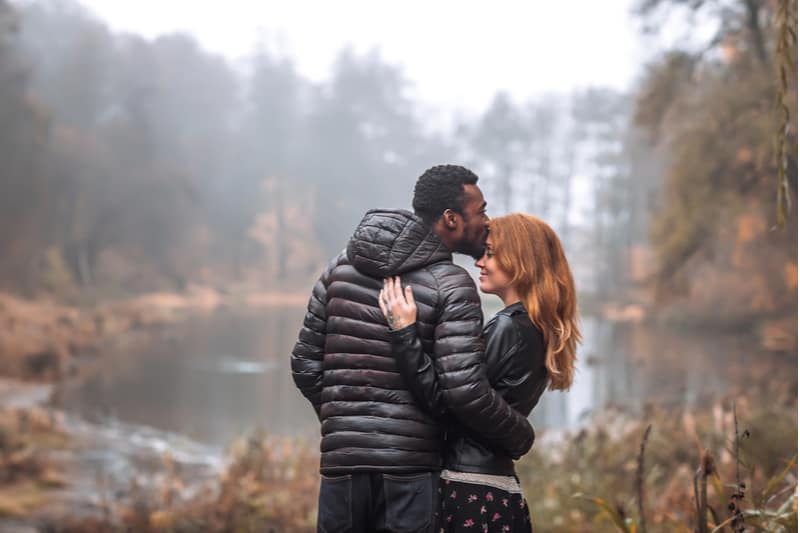 interracial couple posing with autumn leaves background