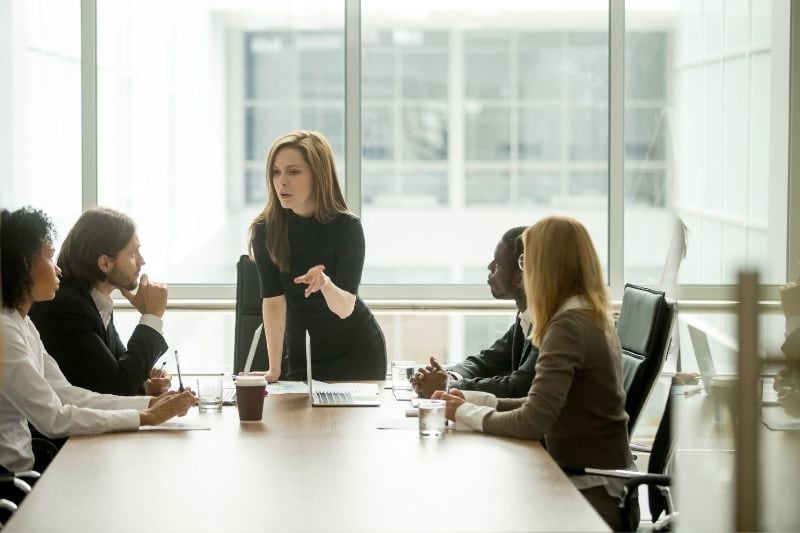 lady boss standing in front of a multiracial colleagues instructing inside the meeting room