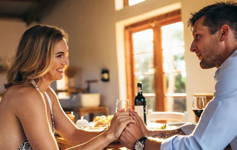 love young couple dining indoors holding hands during the day