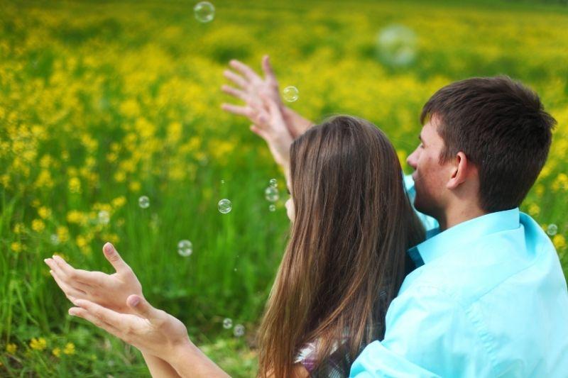 lovers enjoying bubbles in the yellow flower garden