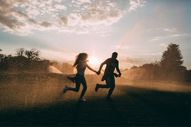 lovers runnung in rain spray during sunset in silhouette