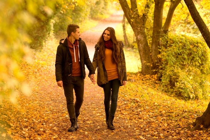 lovers walking holding hand in the middle of the autumn park