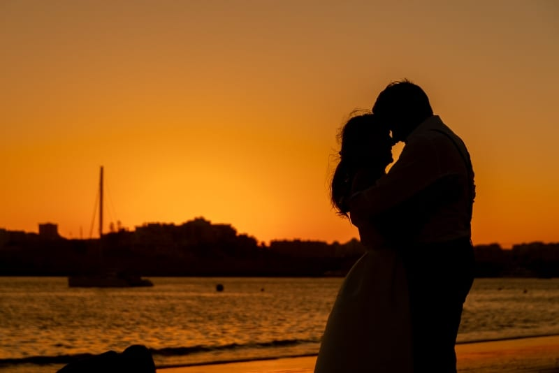 man and woman about to kiss during sunset