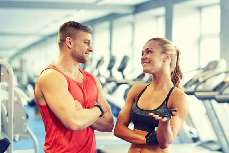 man and woman in the gym talking wearing athletic wear