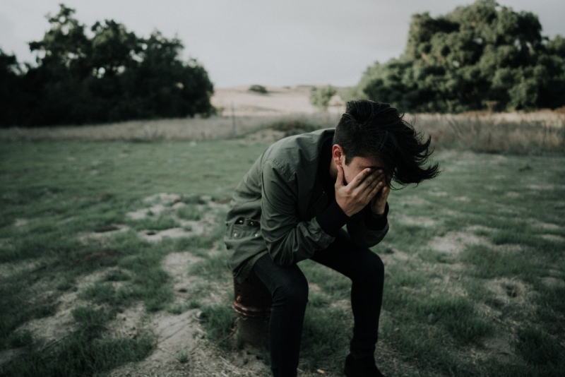 man crying while sitting outdoor