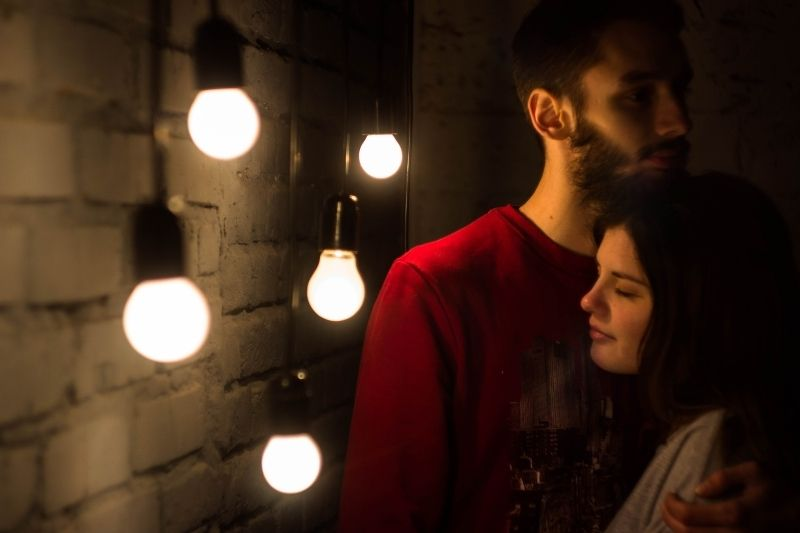 man embracing the woman beside the wall with a series of incandescent bulb