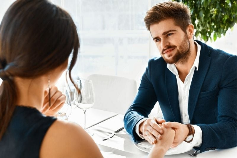 man holding the woman's hand while sitting on table during dinner date