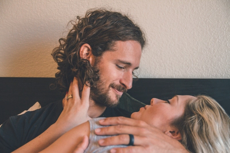 man holding woman while sitting on bed